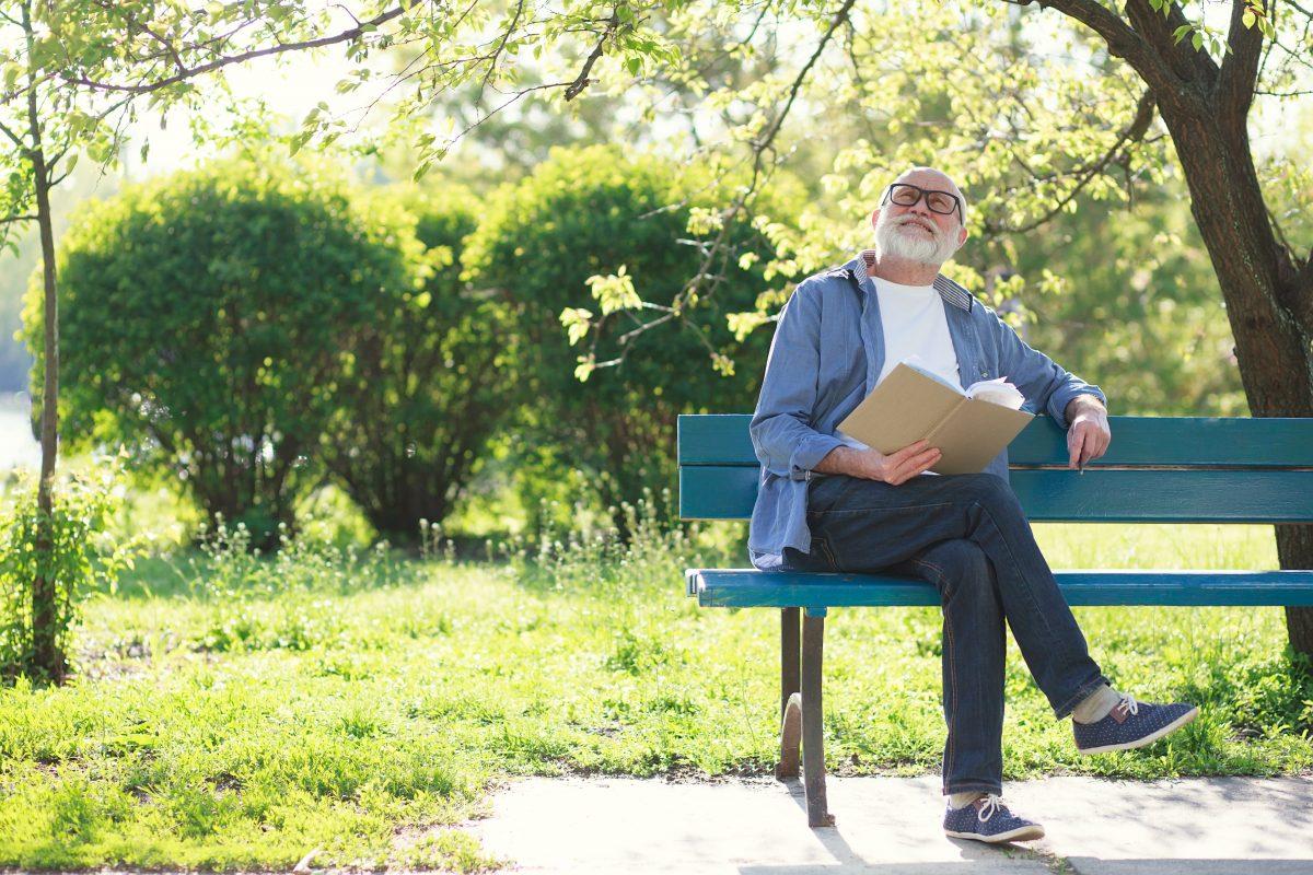 Senior im Park auf Parkbank
