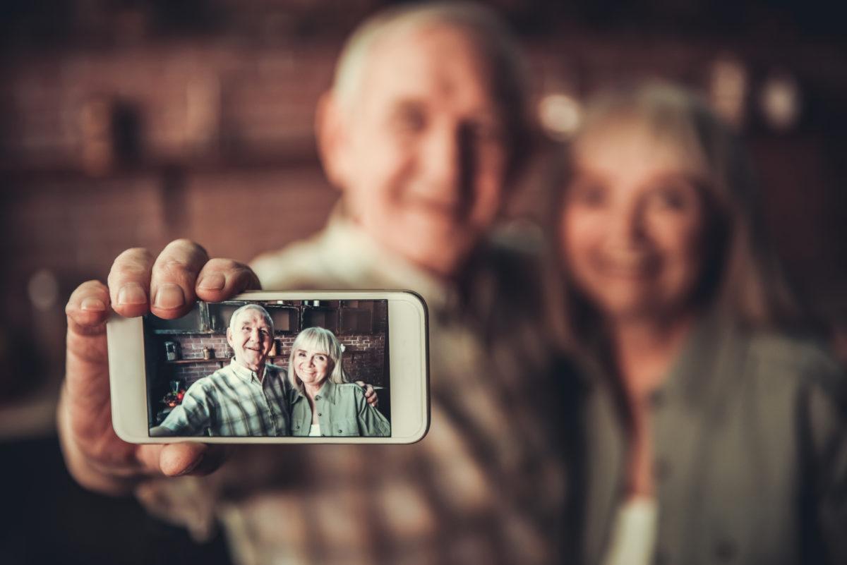 Senior mit Handy macht Selfie