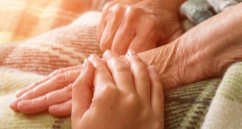 Pflegerhand auf Senioren Hand
