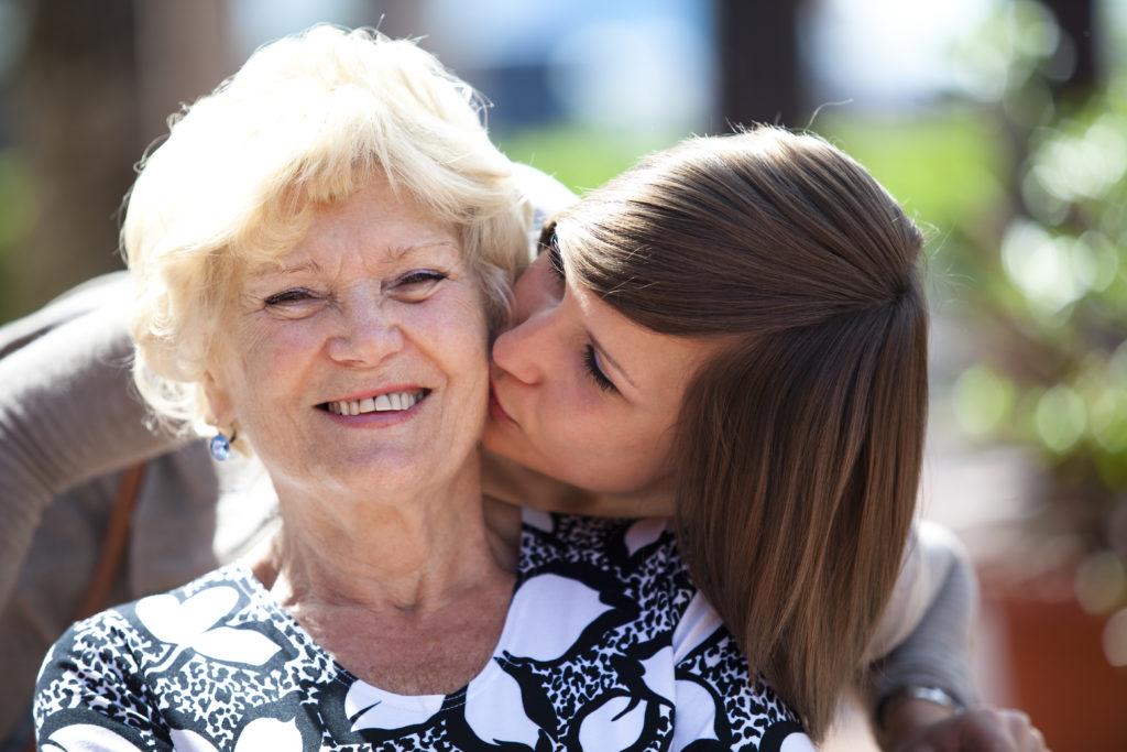 Tochter küsst Seniorin