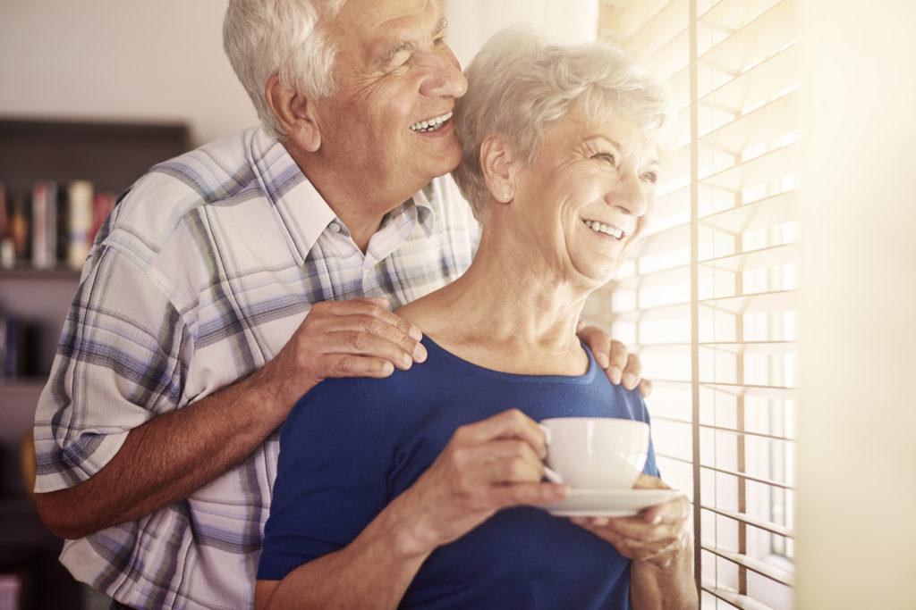 Senior mit Seniorin im Arm vorm Fenster